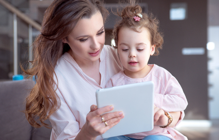 Pretty mother playing tablet with a daughter