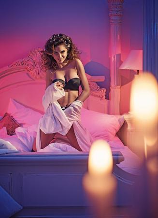 Donna brunetta voluttuosa in una camera da letto romantica Archivio Fotografico