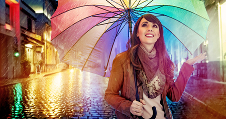 blue green background: Fashionable brunette lady with a colorful umbrella Stock Photo