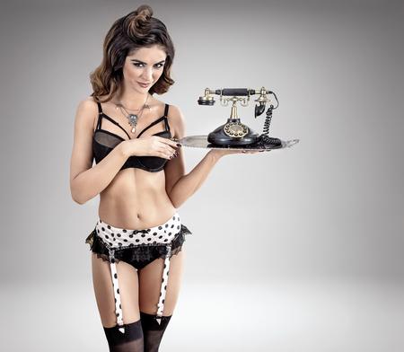 Cameriera sensuale che tiene un telefono dell'annata