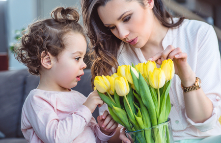 Beautiful mother showing tulips to her little daughter Stock Photo