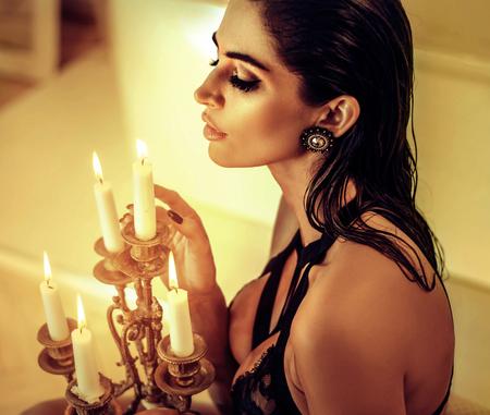 Donna seducente bruna che tiene un candeliere