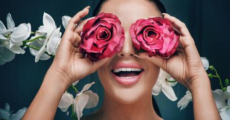 Ritratto di una donna elegante che tiene le rose rosse
