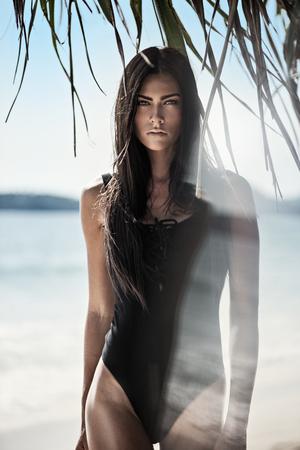 Bella donna bruna sulla spiaggia tropicale