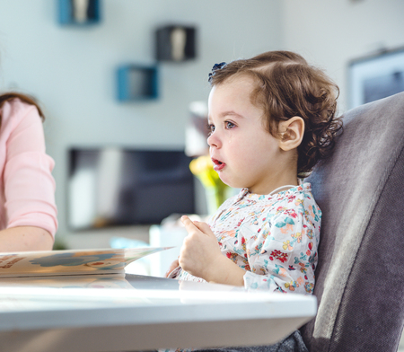 Woman reading a book to her cute daughter Stock Photo
