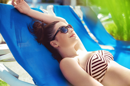 resting: Brunette woman relaxing at the hotels swimming pool Stock Photo