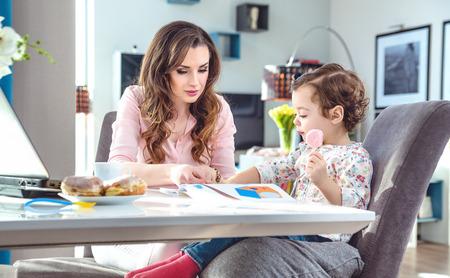 Bella giovane madre che legge a una piccola figlia photo