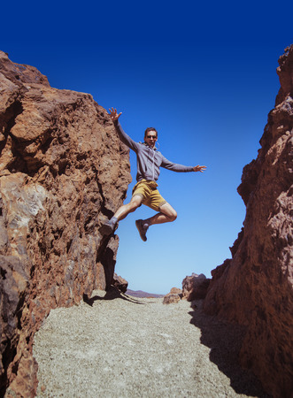 Athletic guy running on the desert mountains Stock Photo