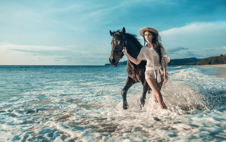 Cheerful, sensual woman walking with a horse Stock Photo
