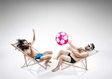 Due amici divertenti seduti sulle sedie a sdraio photo