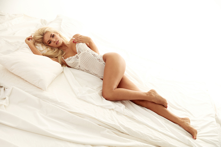 Adorable blond lady resting in the luxurious, brigt bedroom Archivio Fotografico