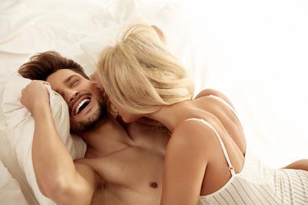 Giovane coppia allegra che riposa nella camera dell'hotel