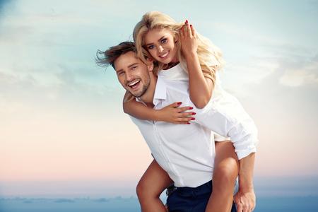 Handsome guy carrying his girlfriend piggyback