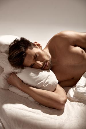 Bello, adatto all'uomo rilassante a letto