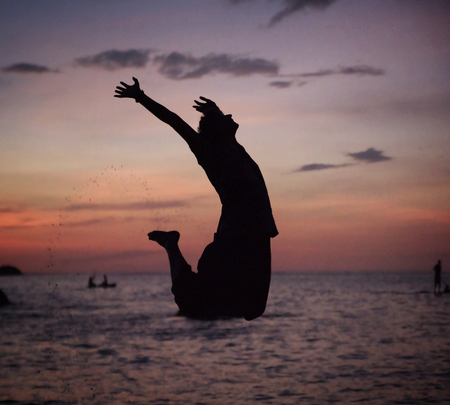 Silhouette of a relaxed, young man jumping on the beach photo