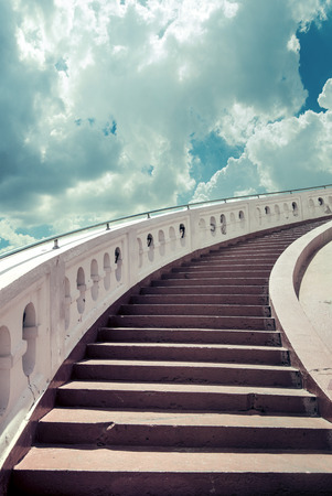 Stairs towards blue sky with fluffy clouds