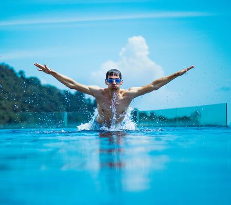 Young, muscular swimmer splashing water - summer shot photo