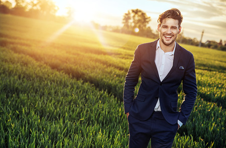 Optimistic, young businessman relaxing on the wheat field Archivio Fotografico