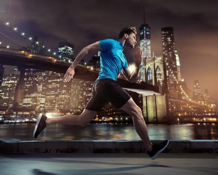 Bel giovane jogging che attraversa la città durante la notte