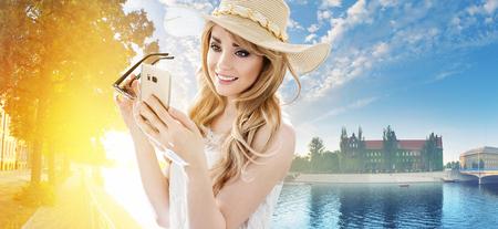 Ritratto di una bella donna bionda utilizzando uno smartphone photo