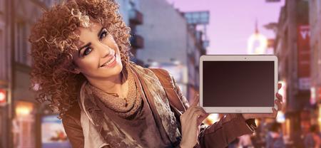 Closeup ritratto di una giovane donna graziosa con un dispositivo elettronico