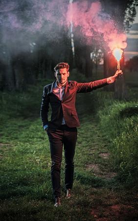 Ritratto concettuale di un giovane imprenditore in possesso di un bruciore flare