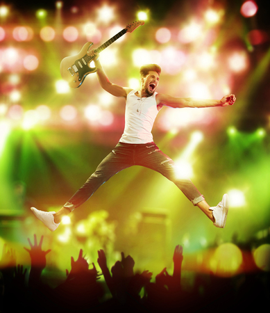 Young and handsome guitarist jumping on the stage Stock Photo