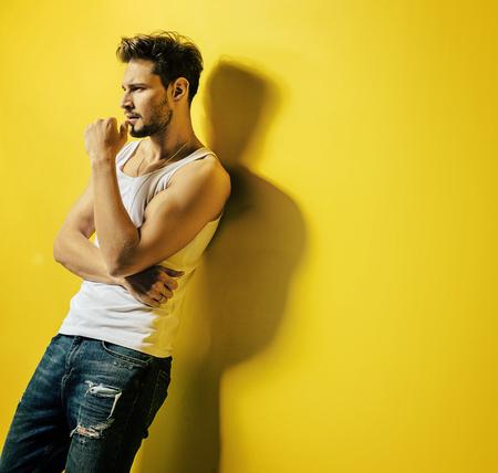 Bel giovane, appoggiato alla luminosa parete gialla