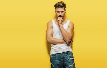 Bello, ragazzo muscolare che presenta su uno sfondo giallo