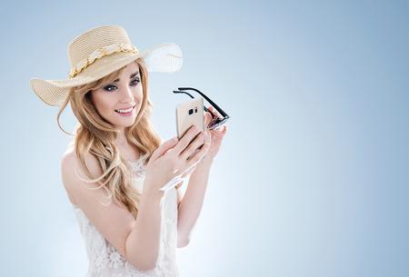 Bella bionda con un telefono cellulare photo