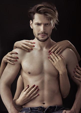 Bel, giovane uomo toccato da molte mani femminili