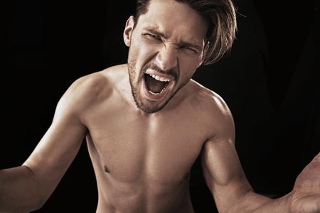 Aggressivo ragazzo urlando in posa su uno sfondo nero