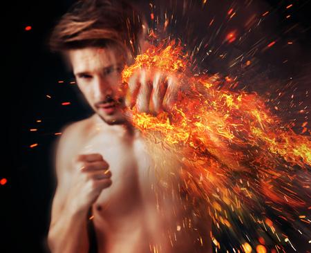 Atleta bello che punta con la fiamma intorno al braccio muscolare