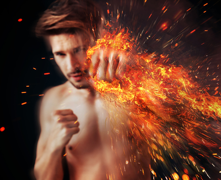 Handsome athlete punching with flame around his muscular arm