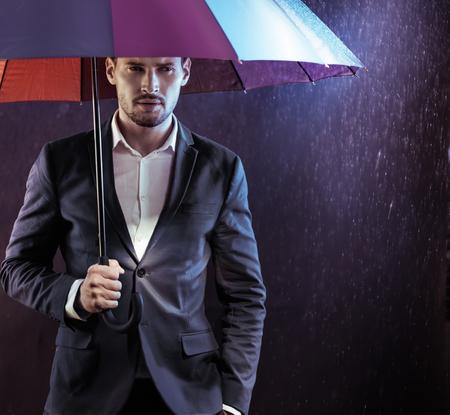 Ritratto di un uomo d'affari serio e calmo in possesso di un ombrello colorato