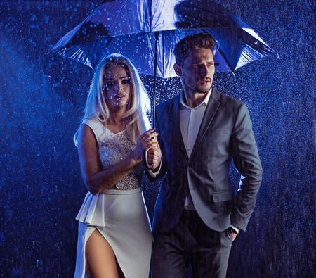 Ritratto di stile di moda di una giovane coppia che presentano nel tempo piovoso