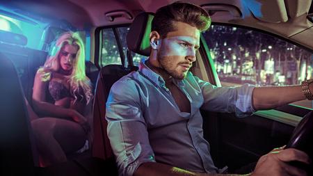 Sexy koppel in een elegant voertuig, 's nachts Stockfoto