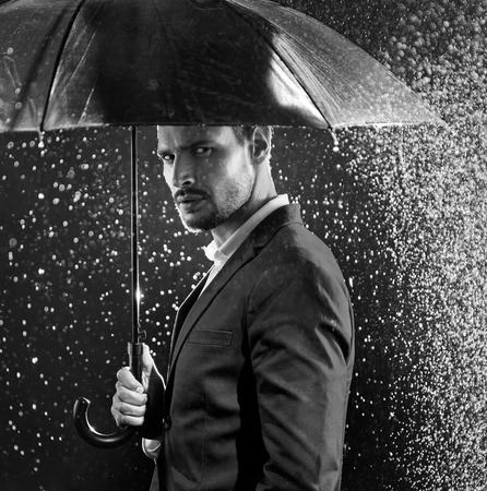 Ritratto in bianco e nero di un uomo che propone al centro della tempesta