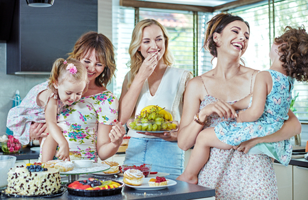 Cheerful young women eating cakes and sweets with their children