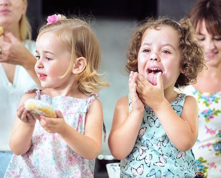 Due ragazze carine che mangiano dolci e gustose ciambelle Archivio Fotografico