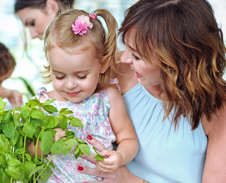 Mother showing her beloved daughter the fresh herbs