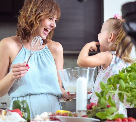 Mother and daughter preparing a tasty summer breakfast together