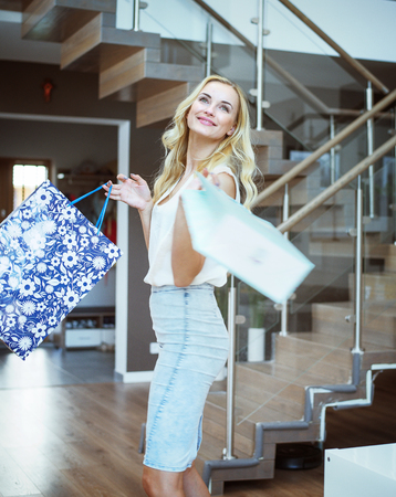 Blond, pretty woman holding shopping bags