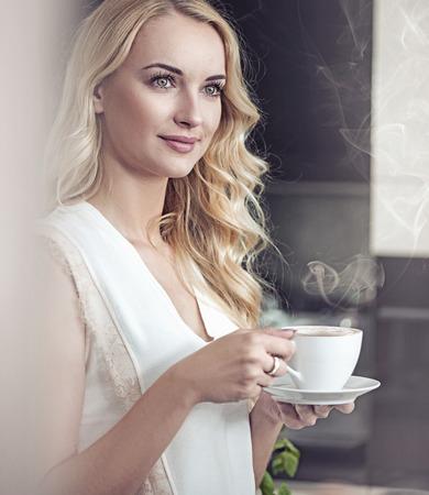 한 잔의 커피를 마시는 예쁜 금발 아가씨의 초상