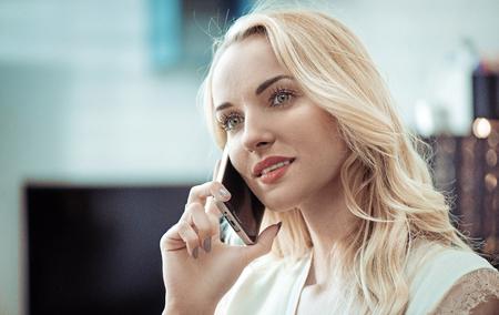 Closeup ritratto di una bella donna bionda utilizzando uno smartphone