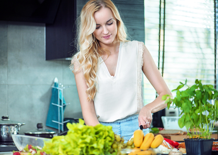 Blond young woman preparing a dinner dish