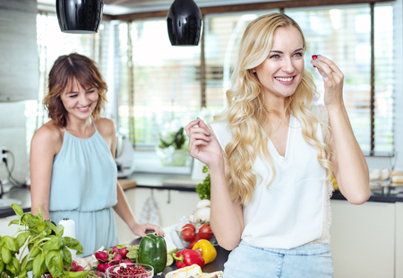 Due amiche allegre rilassanti nella luminosa cucina