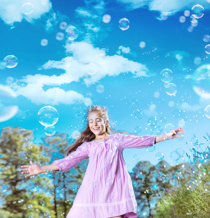 Portrait of a pretty young girl dancing among lots of soap bubbles