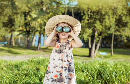 Portrait of a cheerful, little child  looking through the binoculars