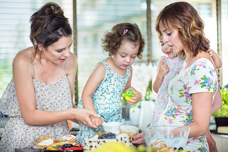 Young mothers making a cake with their cute daughters